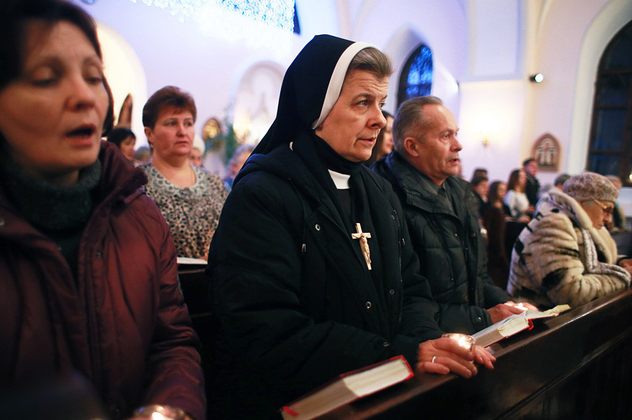 Believers attend a traditional Christmas Eve Mass at the Roman Catholic Church of the Blessed Virgin Mary of the Rosary.