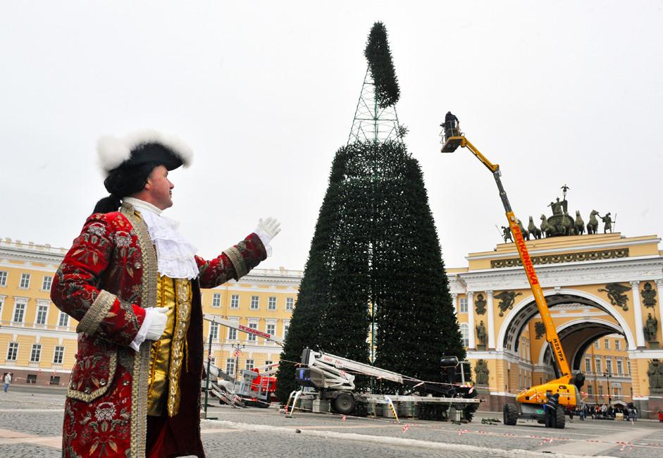 """Поставување на елка на плоштадот """"Дворцоваја"""" во Санкт Петербург. На фотографијата: човек во историски костим од времето на Петар Велики."""