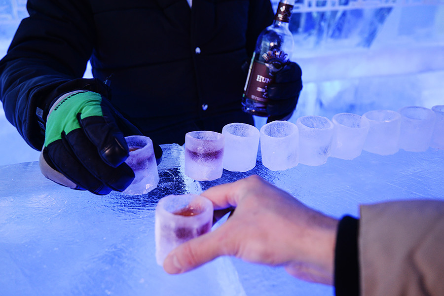A bartender pours beverage into ice glasses at Twiggy ice bar in Novosibirsk.