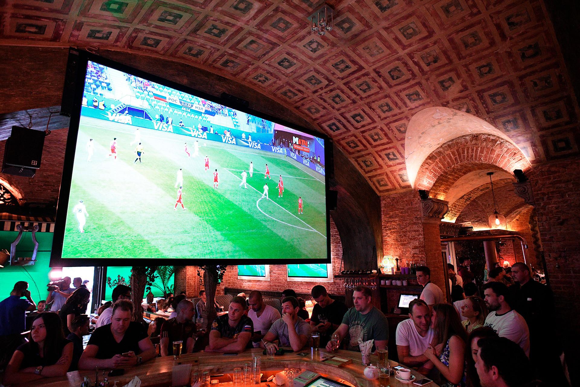 Penggemar sepak bola menyaksikan seremoni pembukaan Piala Konfederasi FIFA 2017 di pub Liga Pap di Moskow.