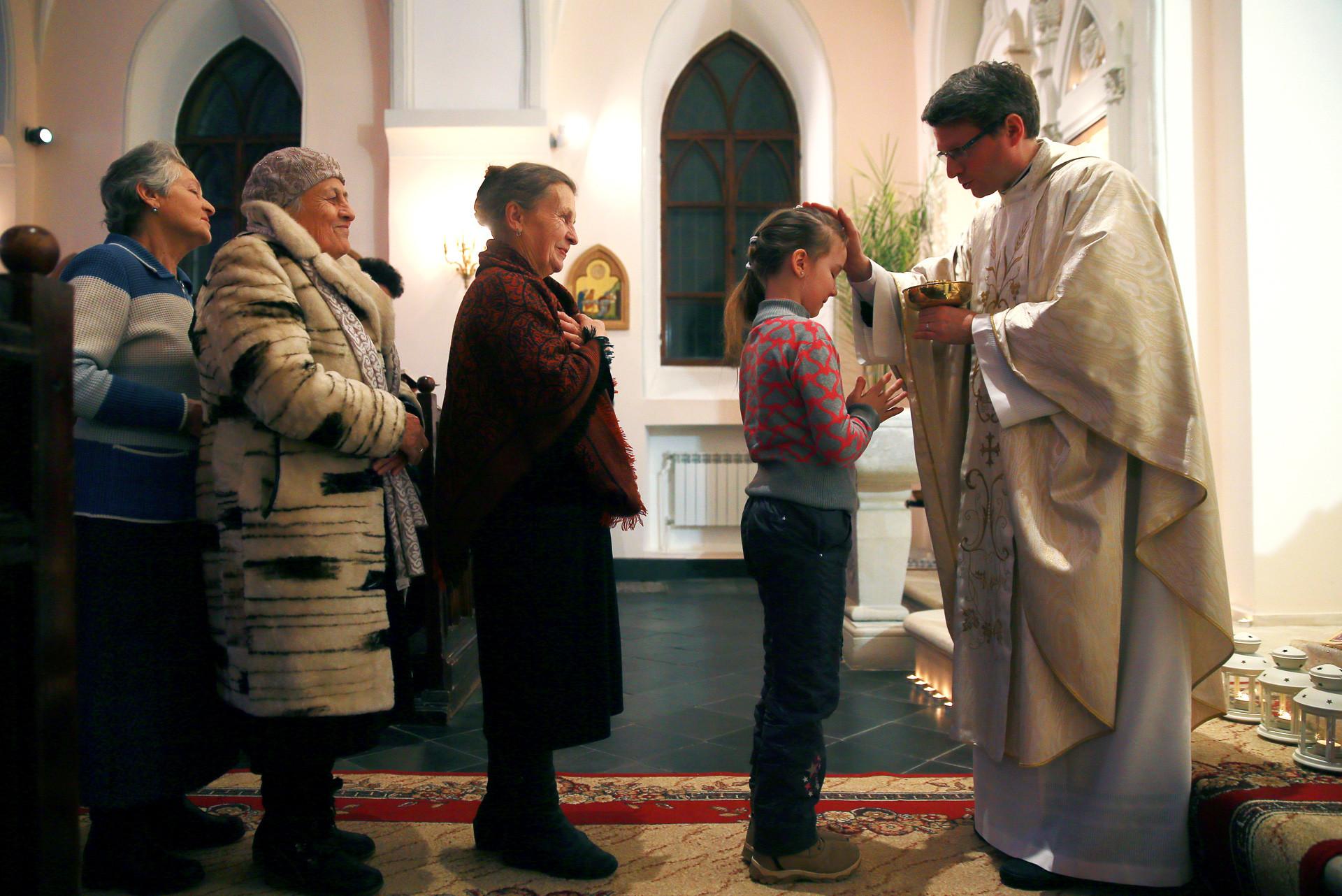 Un grupo de creyentes asiste a la tradicional misa de víspera de Navidad en la Iglesia de Nuestra Señora del Rosario en Vladímir.