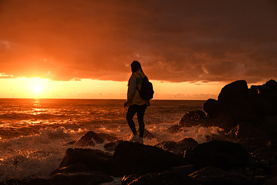 A girl participating in the 19th World Festival of Youth and Students stands on the shore of the Black Sea at dawn.