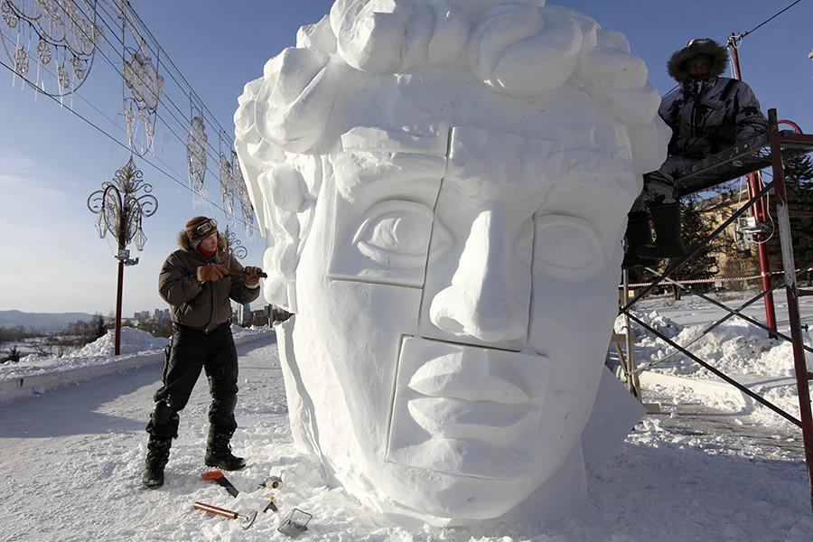"""Membros de uma equipe da cidade de Perm, nos Urais, trabalham em escultura de gelo durante o primeiro festival internacional de esculturas de neve e gelo """"Gelo Mágico da Sibéria"""", em Krasnkoiarsk."""