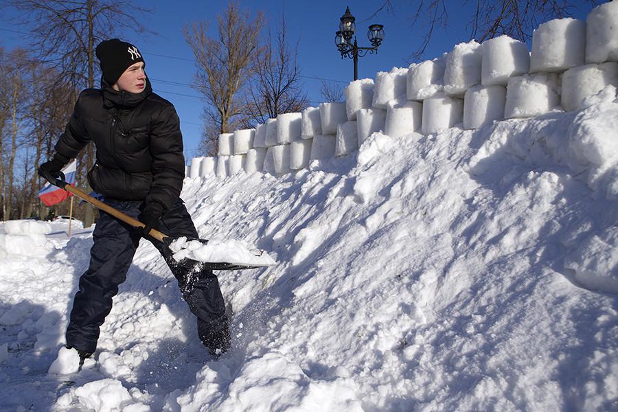 Habitante local fortifica a parede de uma fortaleza de neve em Ribinsk.