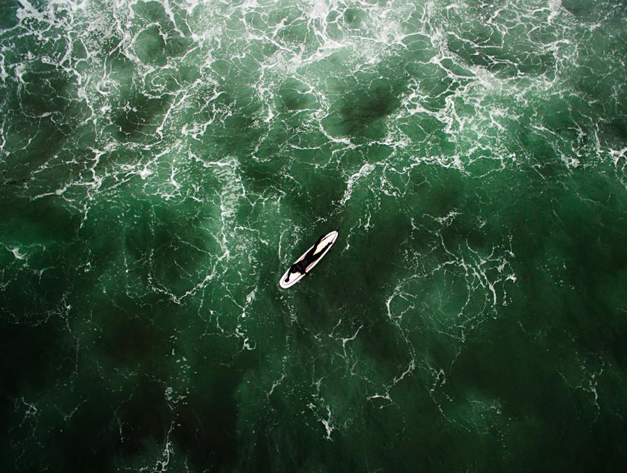 ロシア太平洋岸ウスリー湾のルースキー島沖の波に乗るサーファー