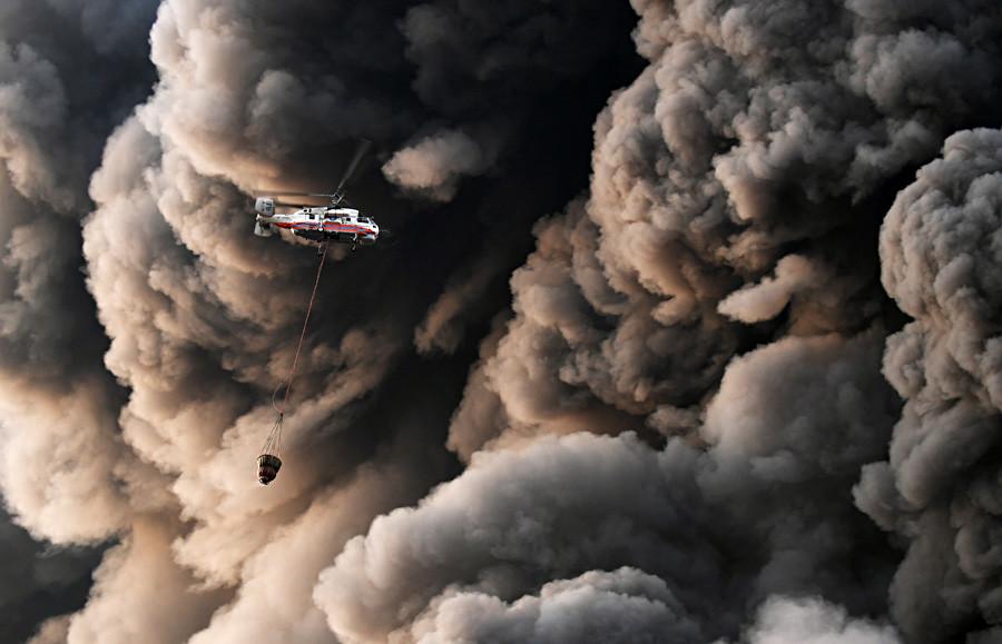 モスクワ西部の郊外のショッピングモールで起きた火災を消防隊が消し止めようとする中、もうもうと立ちこめる煙を横切って水を運ぶロシアの緊急ヘリコプター