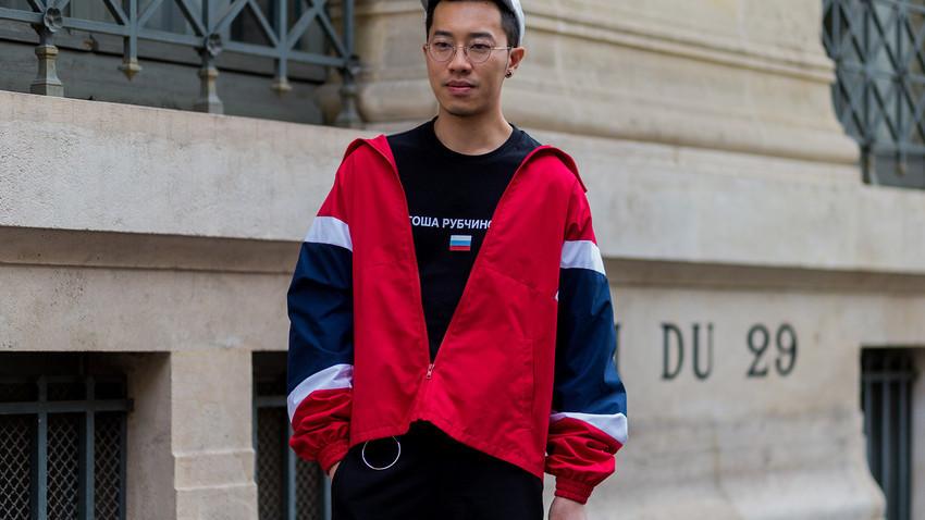 Seorang pengunjung memakai sweter dan jaket Gosha Rubchinskiy saat Paris Fashion Week 2017.
