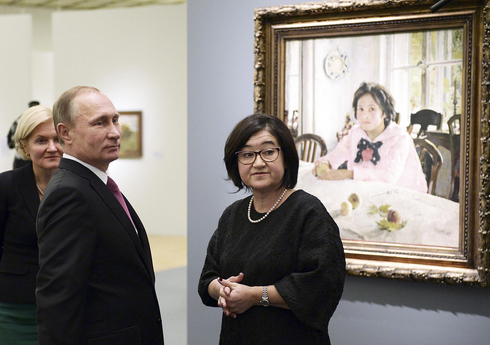 Vladimir Putin mendengarkan Direktur Galeri Nasional Tretyakov Zelfira Tregulova saat ia mengunjungi pameran seniman Valentin Serov.