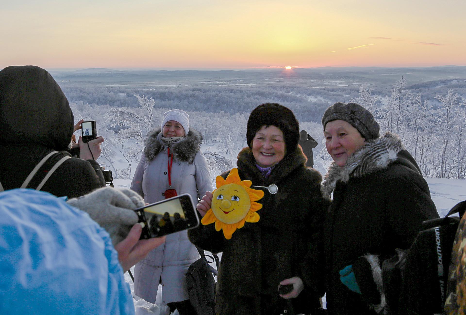 40日ぶりの日の出を背景に写真を撮るムルマンスクの住民。