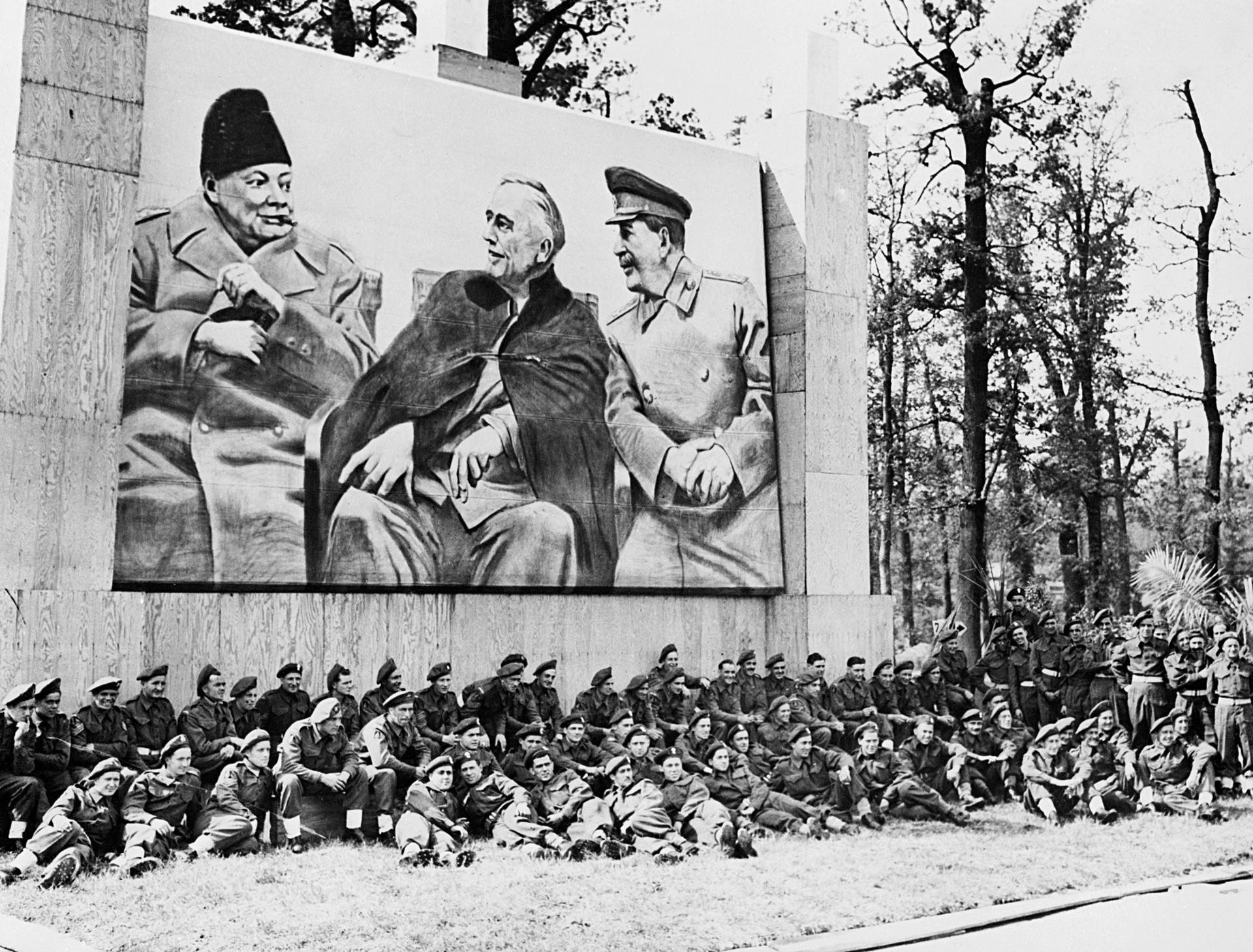 Британски војници, учесници Параде победе савезника у Берлину, одмарају се испод великог плаката са портретима Черчила, Рузвелта и Стаљина у Јалти.