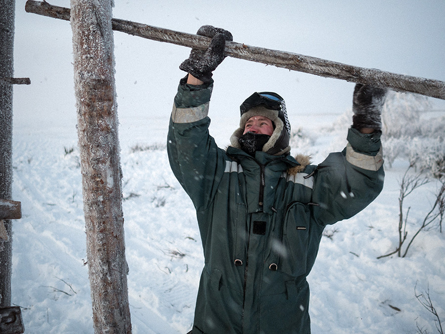 Andrey closes the barrier after the reindeer have been herded from the tundra into the paddock. He sometimes spends weeks or months alone in the tundra minding the herd and repairing wooden installations