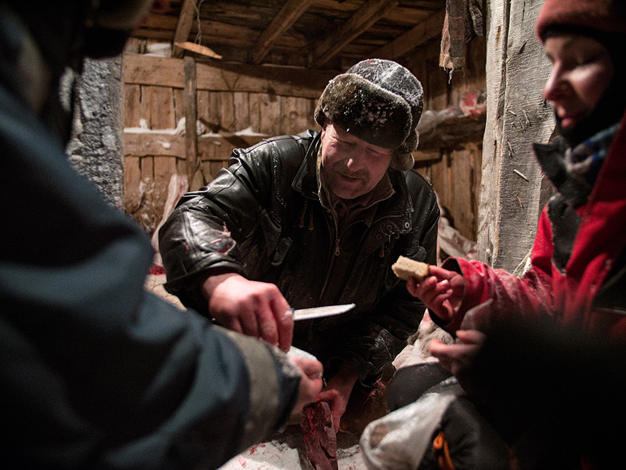 At the Polmos base, Alexander takes a break and shares bone marrow and frozen liver with visitors, crouching in the snow