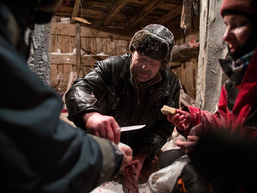 À l'élevage de Polmos, Alexander s'accorde une pause et partage de la moelle et du foie gelé avec les visiteurs, tous accroupis dans la neige.