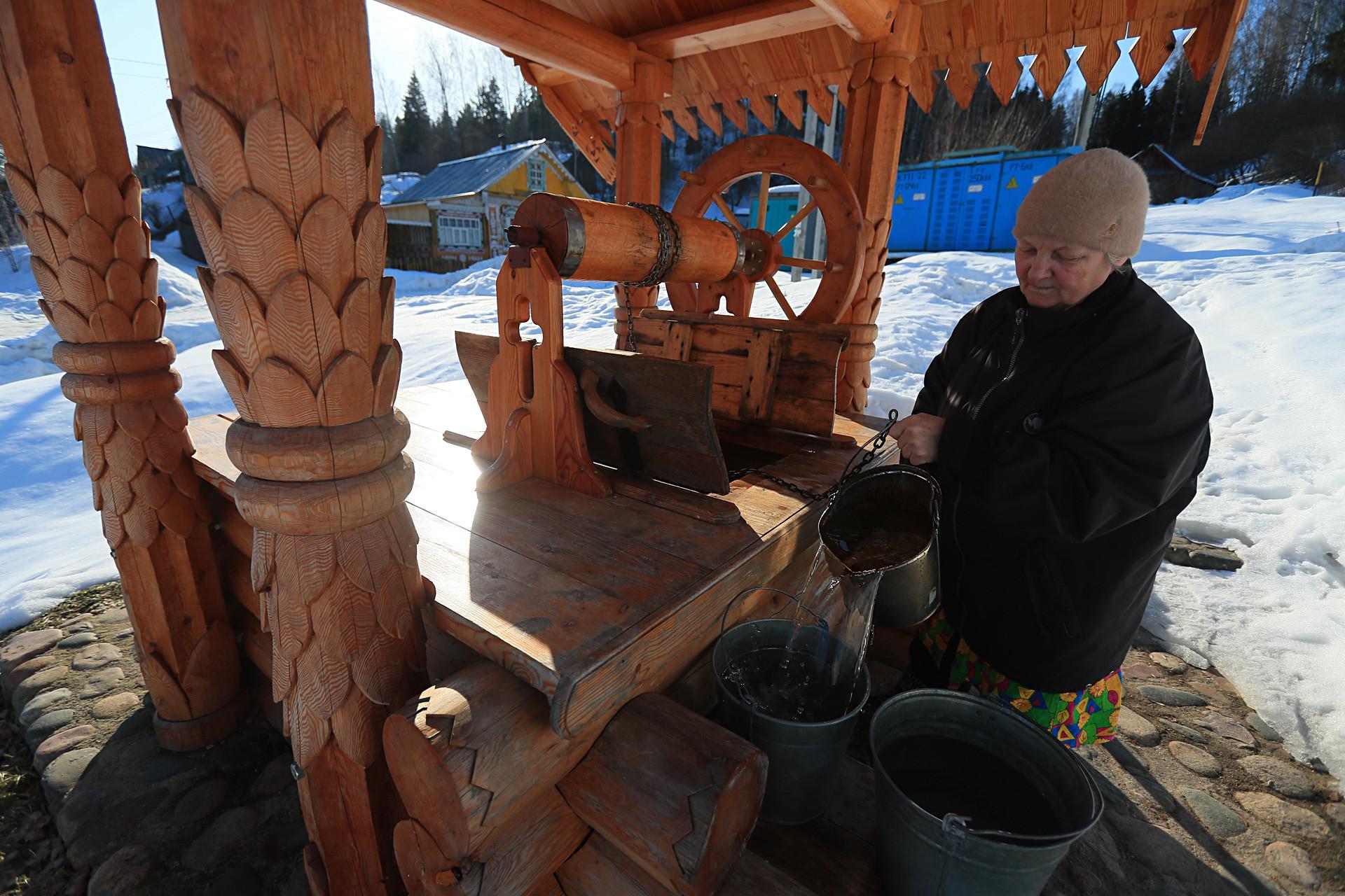 Mulher retira água de um poço na cidade de Plios, na Região de Ivánovo.