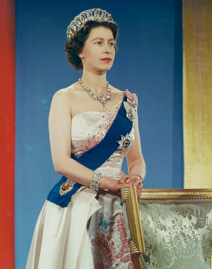 Queen Elizabeth II wearing crown, blue sash and pink gown.