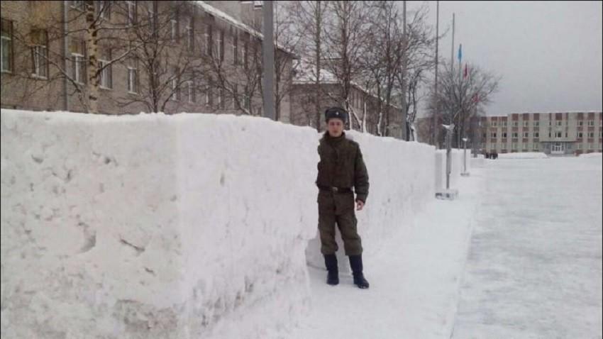 Soldado ante un montón de nieve ordenada.