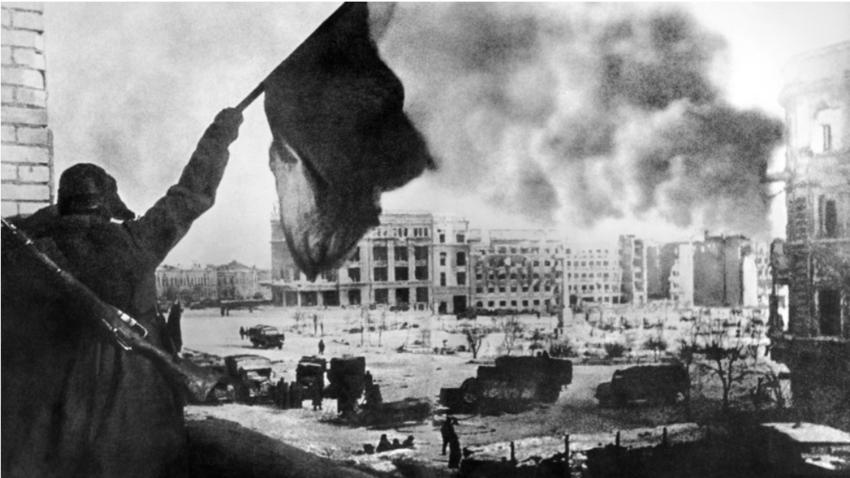 Sovjetski vojak maha z rdečo zastavo sred glavnega mestnega trga v Stalingradu.