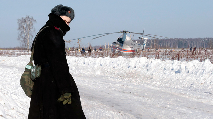 A Russian serviceman looks back as he stands guard during a search operation near the crash site of the short-haul AN-148 airplane operated by Saratov Airlines in Moscow Region.