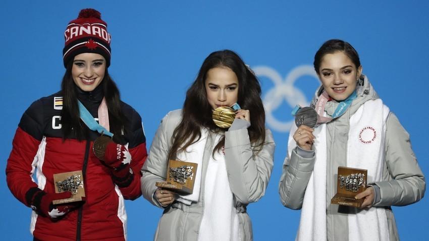 Peraih medali emas Alina Zagitova (tengah), peraih medali perak Evgenia Medvedeva (kanan), dan peraih medali perunggu Kaetlyn Osmond dari Kanada (kiri) di atas podium.