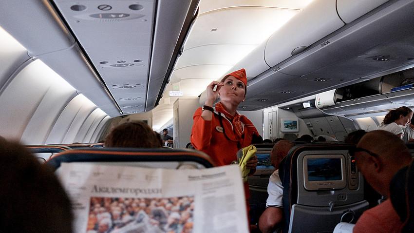 Passengers and a flight attendant aboard an Aeroflot aircraft during flight.