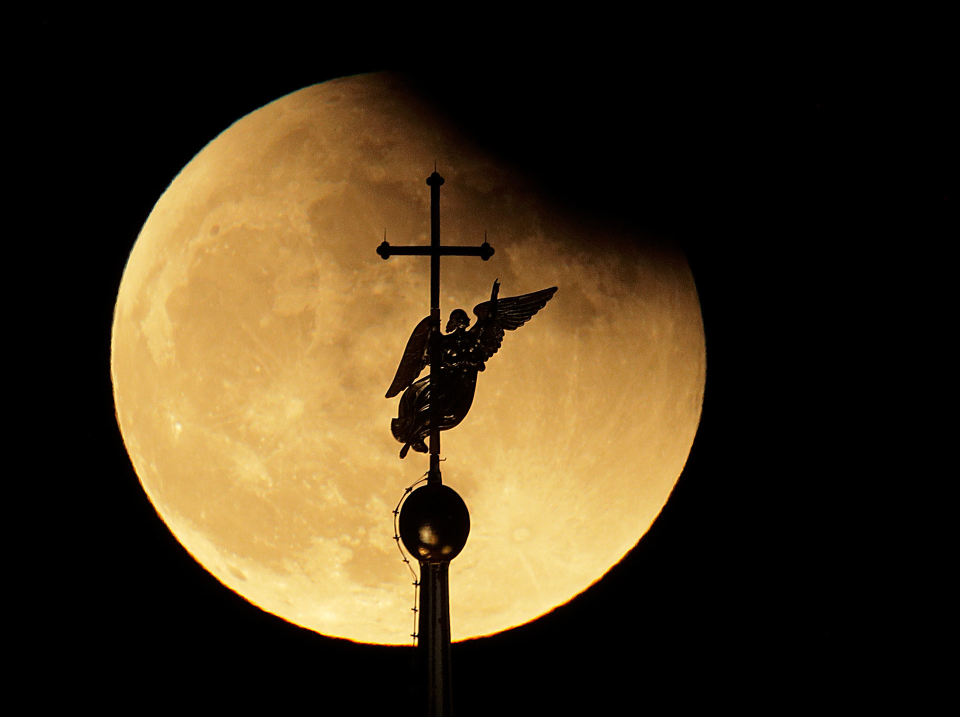 The city landmark weather vane in the form of an Angel, fixed atop a spire of the Saints Peter and Paul Cathedral, is silhouetted against the moon, as seen in St.Petersburg, Russia.