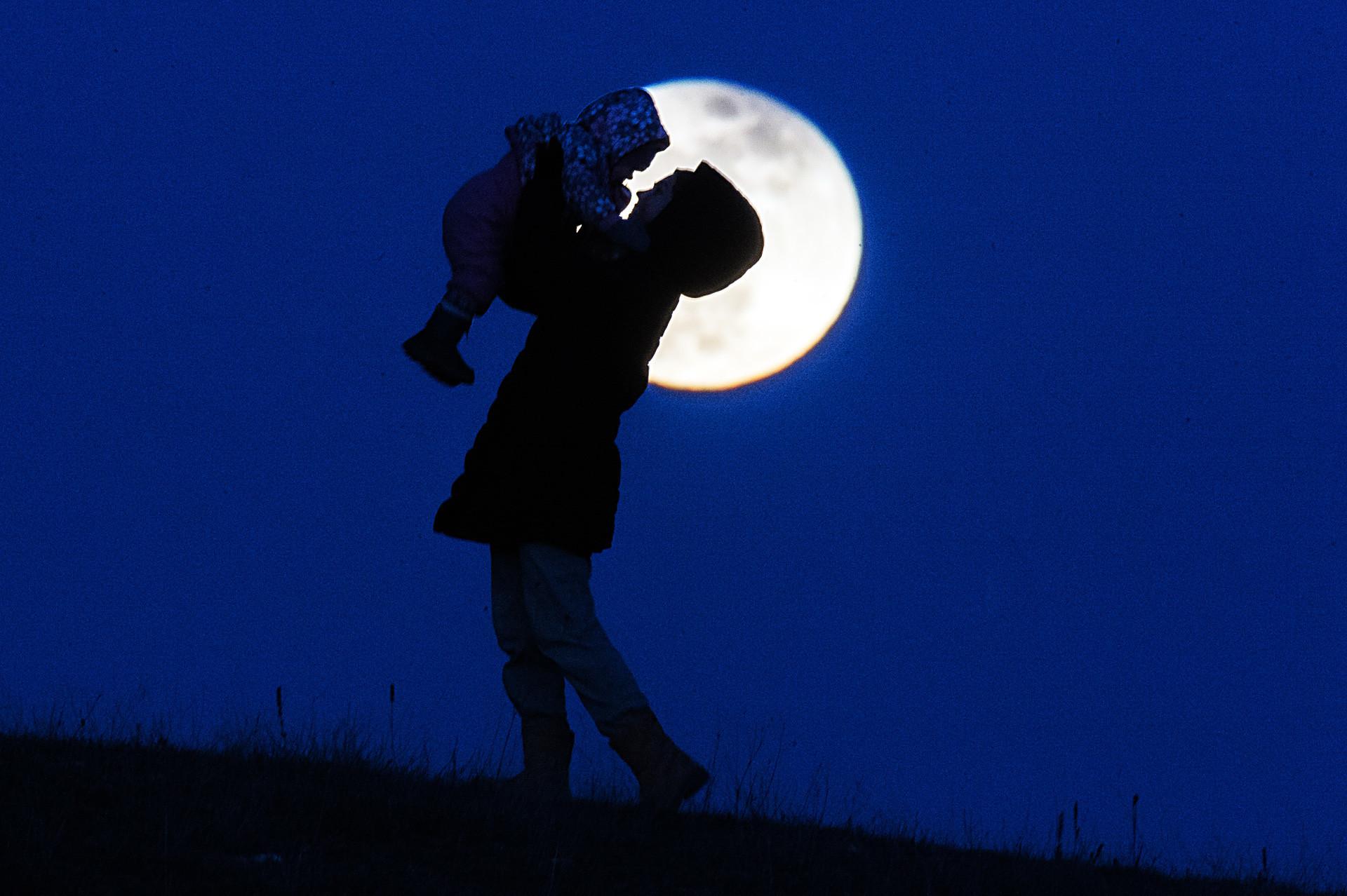 Seorang ibu membawa anaknya berjalan-jalan malam hari di kota Simferopol.