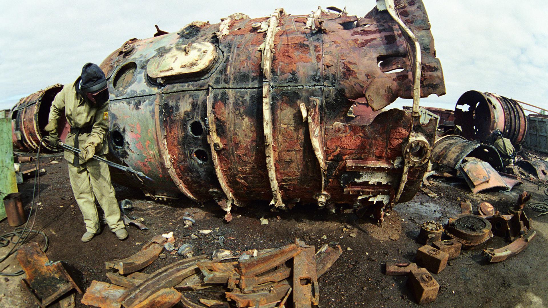Zavarivač u zaštitnom odijelu reže trup podmornice na nuklearni pogon.