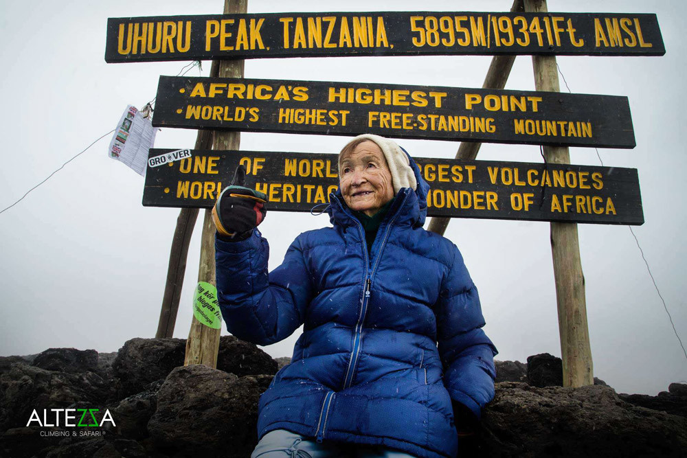 Angela Vorobyova, who just set the new world record, near the Uhuru Peak (the highest point of Kilimanjaro) sign.