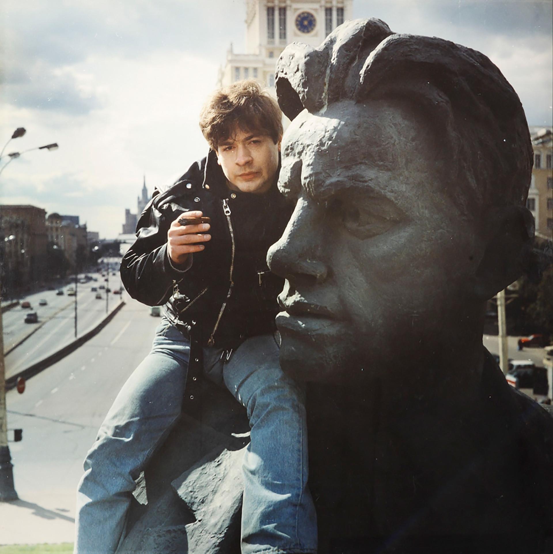 "Anatolij Osmolovskij seduto sul monumento del poeta Vladimir Majakovsksij a Mosca, durante la performance ""Journey of Necesiudik in the land of Brobdingnegs"", del 1993"