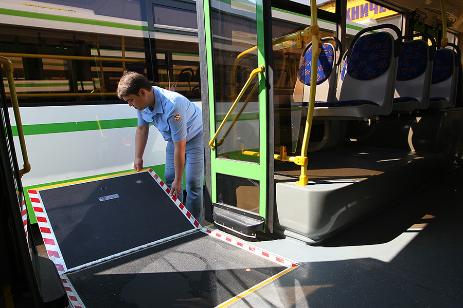 A driver checks the operation of a wheelchair ramp