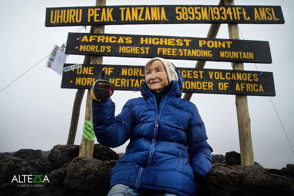 Angela Vorobiova, que acaba de estabelecer um novo recorde mundial, próxima às placas de Uhuru Peak (o ponto mais alto do Kilimanjaro).