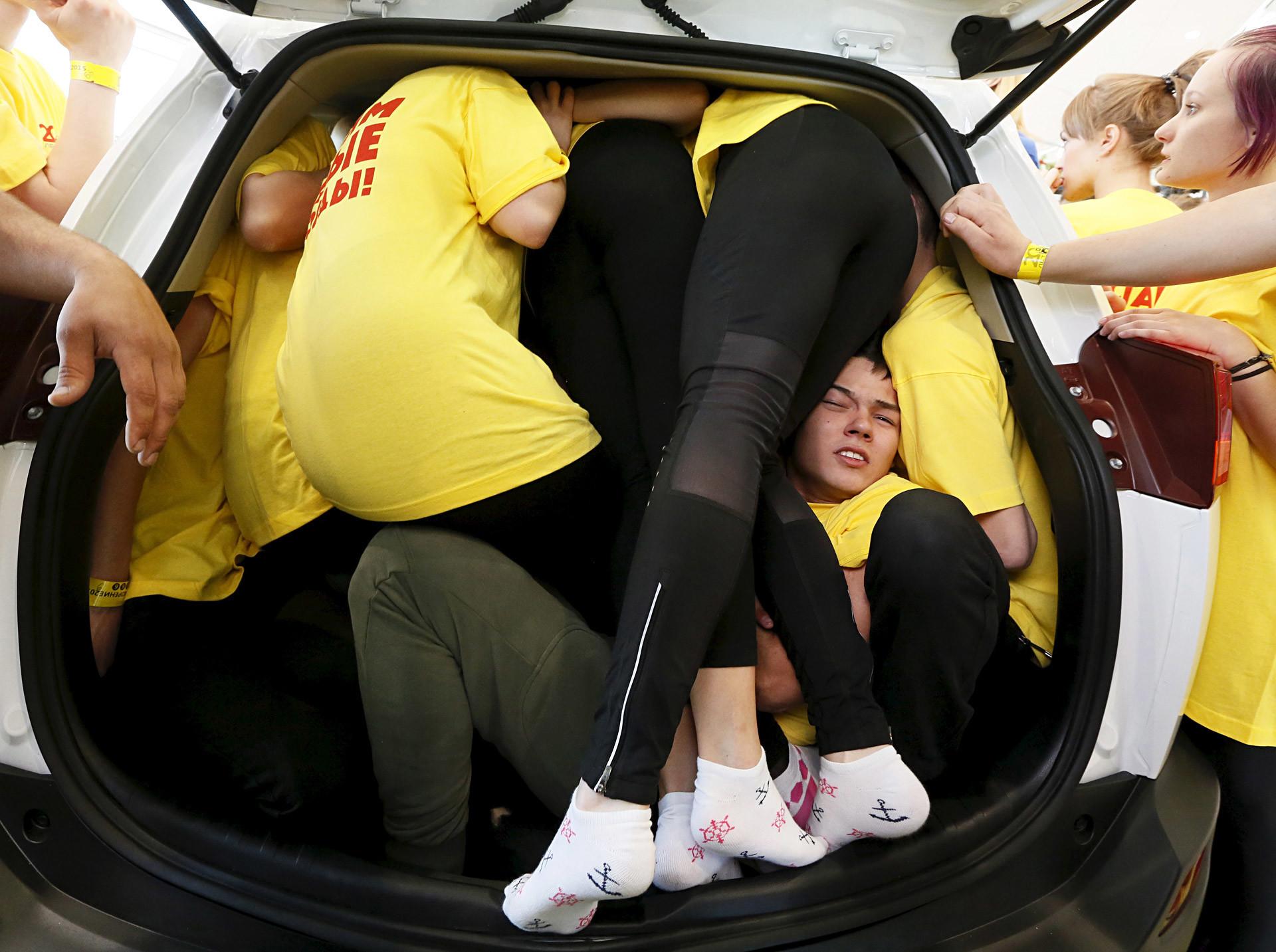 Estudantes da equipe da Universidade Federal Siberiana se espremem dentro de carro durante uma tentativa para o Livro Guinness dos Recordes. A julgar por seus rostos, eles estão transbordando de felicidade!