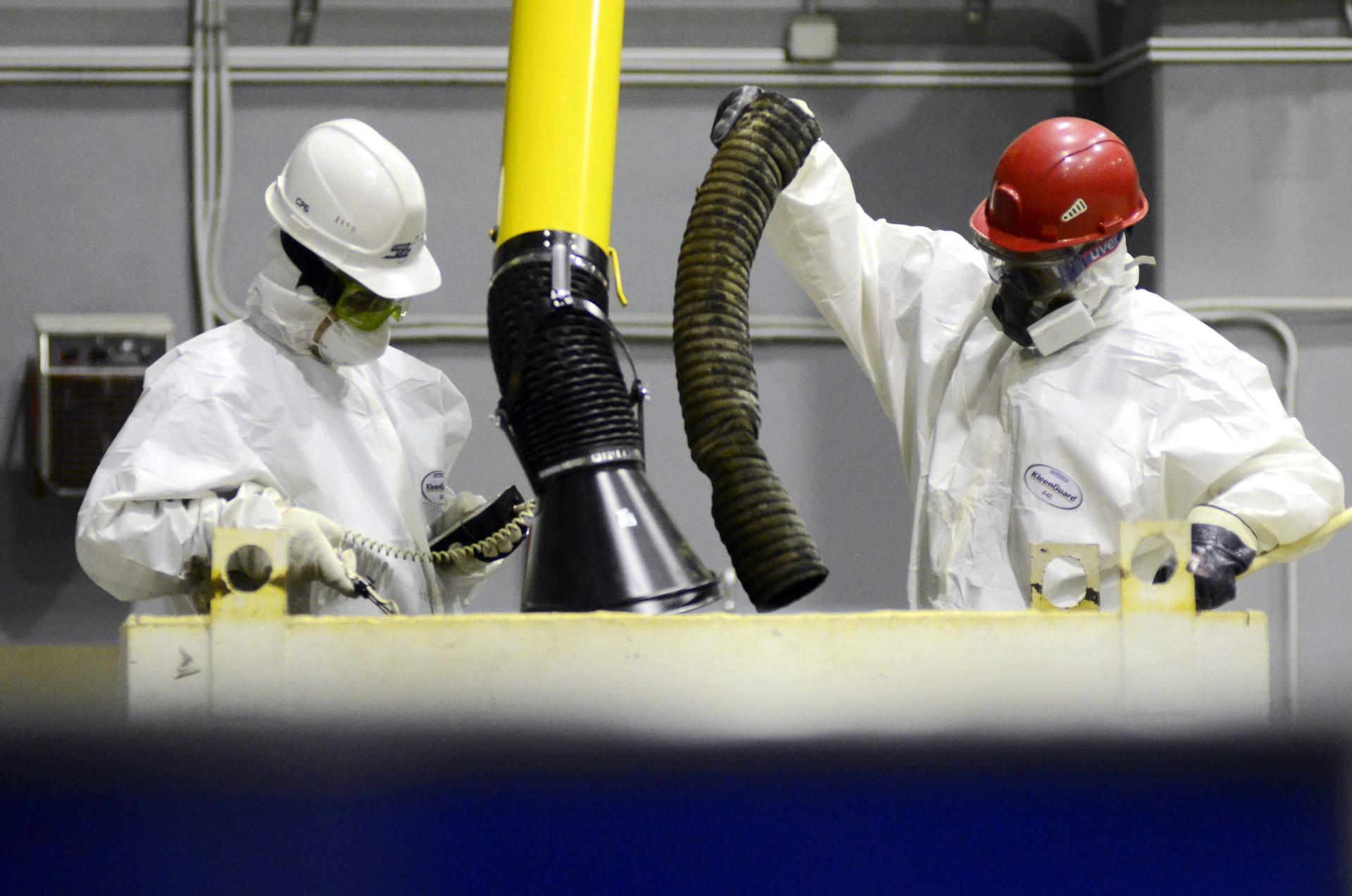 Trabajadores prensan y secan desechos radiactivos sólidos en un taller en la planta de reprocesamiento, acondicionamiento y almacenamiento de desechos radiactivos.