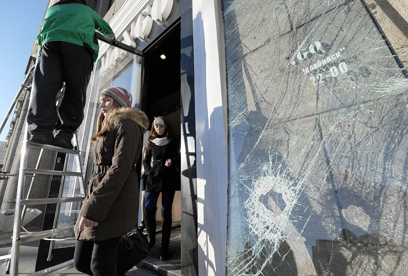 Popravljanje razbitega stekla pri trgovini, ki ga je povzročil udarni val ob eksploziji meteorita