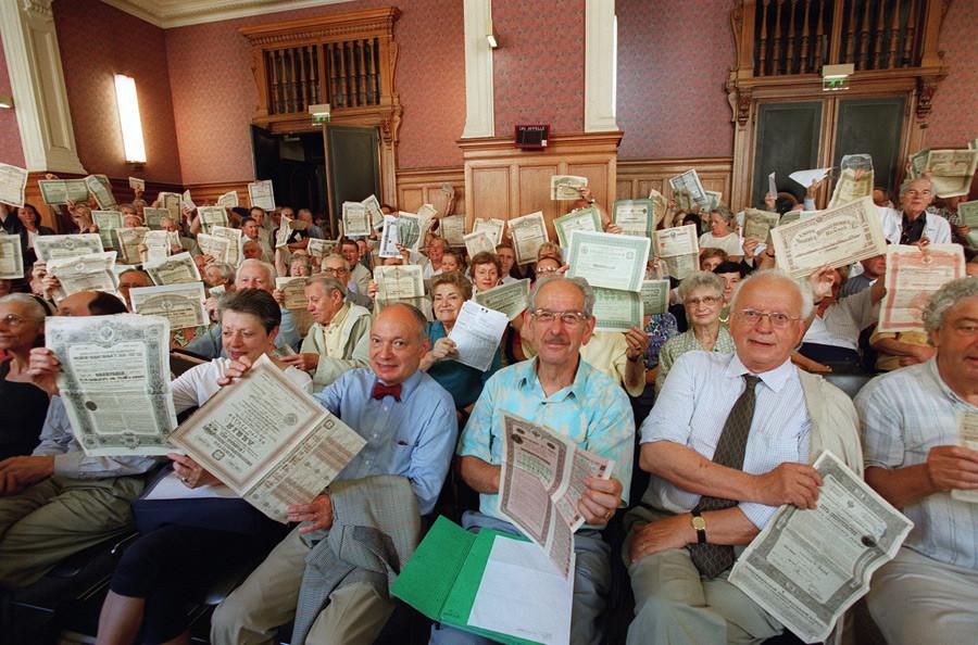 Jezni delničarji ruskih obveznic v rokah držijo svoja potrdila v pariški sodni dvorani, 26. junija 2001.
