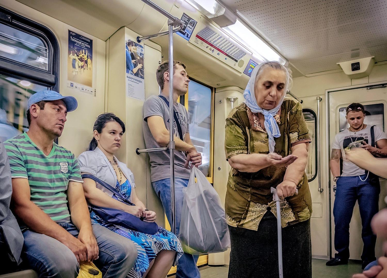 Seorang lansia mengemis di dalam kereta di Moskow.