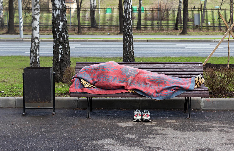 Seorang tunawisma tidur di bangku di Sparrow Hills, Moskow.