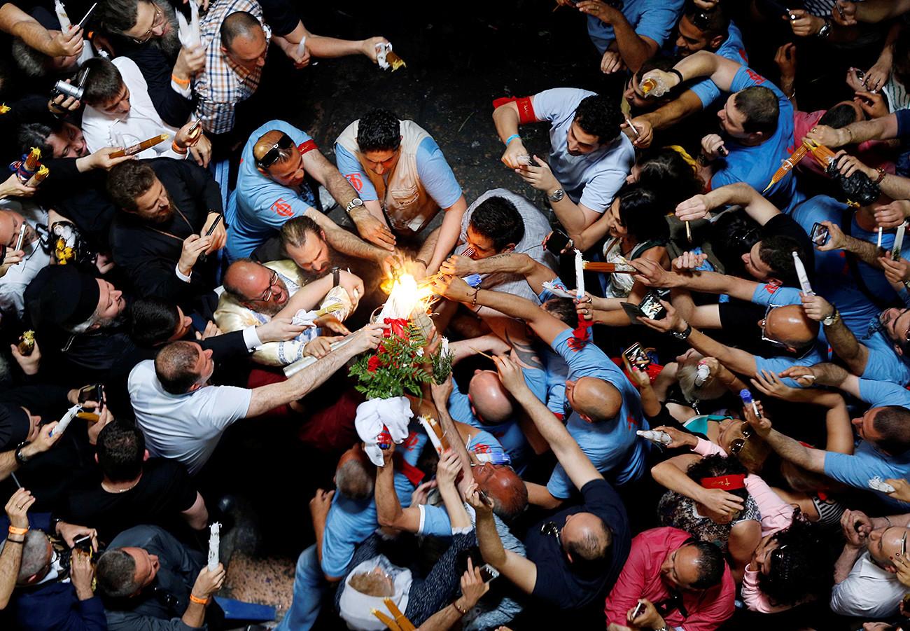 Jemaat menyalakan lilin dalam perayaan Api Suci Ortodoks di Gereja Makam Kudus di Yerusalem.