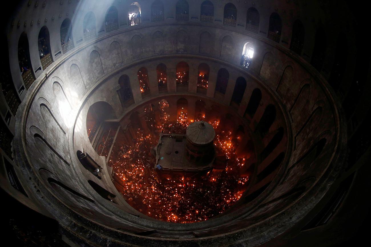 Jemaat memegang lilin dalam perayaan Api Suci Ortodoks di Gereja Makam Kudus, Yerusalem.