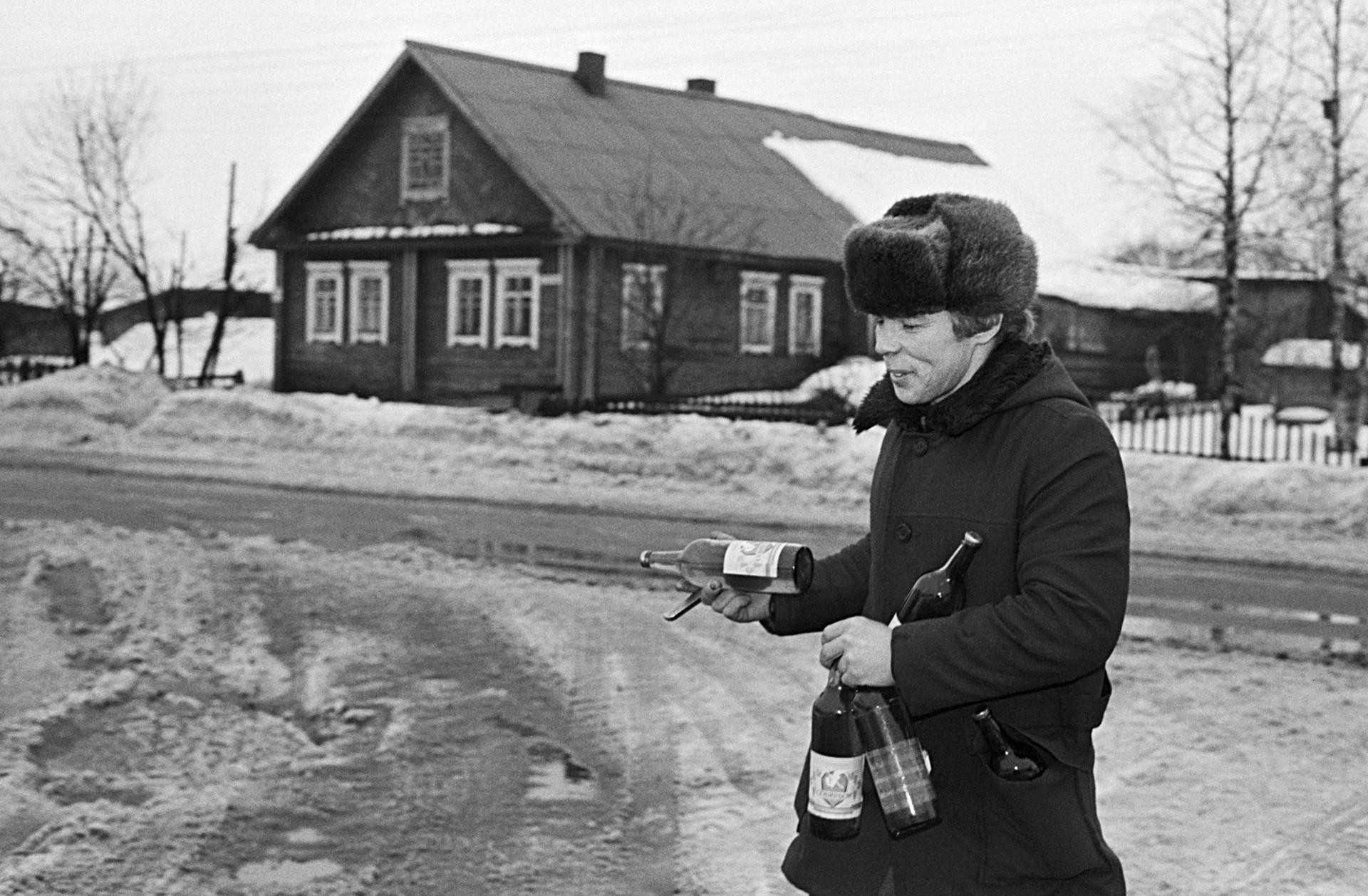 Morador local levando garrafas em uma aldeia soviética em 1990.