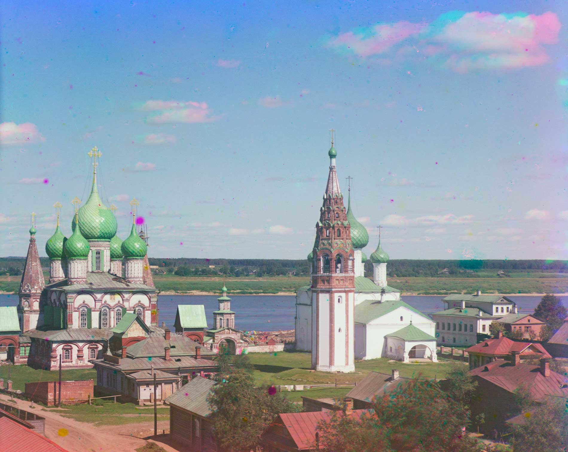 Korovniki ensemble: Church of St. John Chrysostome (left), Holy Gate, bell tower, Church of the Vladimir Icon. Northwest view. Background: Volga River. Mottled appearance of clouds caused by motion during three exposure color process. Summer 1911.