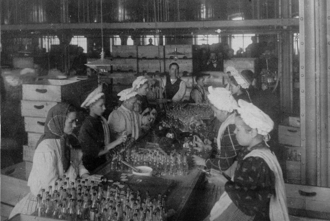Mujeres etiquetando botellas antes de enviarlas al mercado.