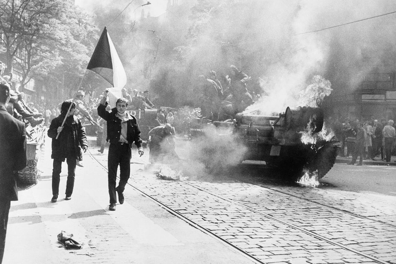 Invasi Soviet ke Cekoslowakia. Warga Cekoslowakia membawa bendera nasional melewati tank yang terbakar di Praha, 1968.