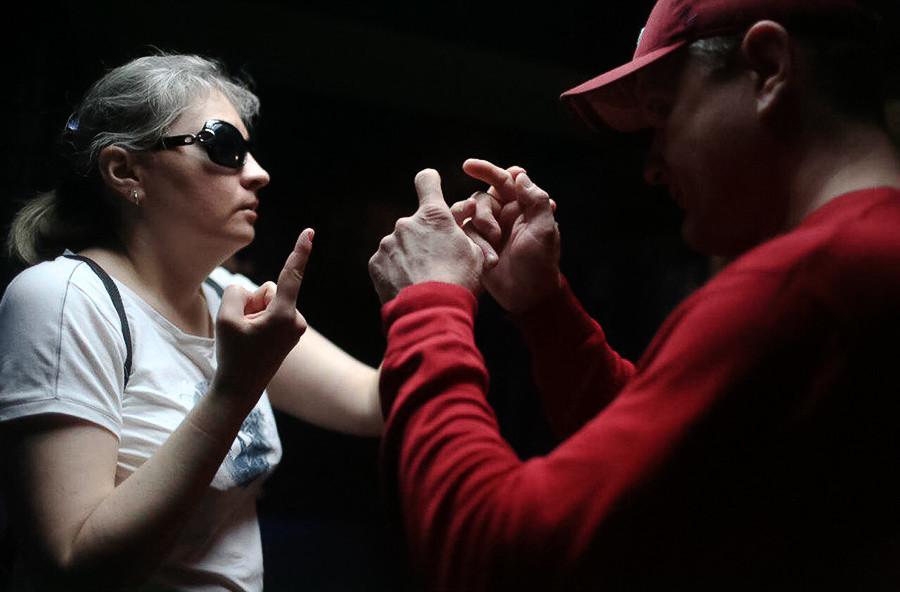 Os surdocegos Lyubov Zhukova e Ruslan Kuleshov se comunicam usando linguagem de gestos.