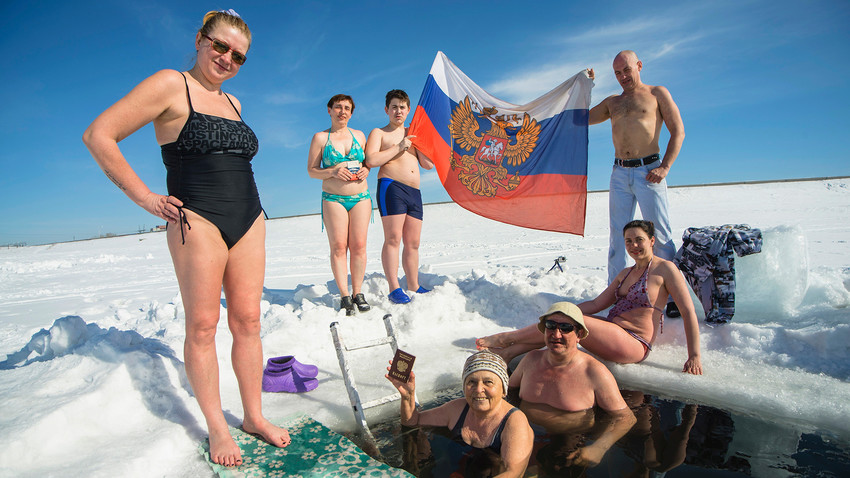 Russian winter swimming enthusiast pose for a photo, displaying a Russian national flag as they celebrate on the day of the Russian presidential election day in Novosibirsk, Russia.