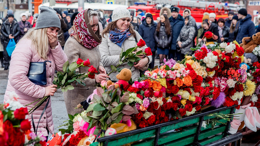People lay flowers for the victims of a fire in a multi-story shopping center in the Siberian city of Kemerovo, Russia