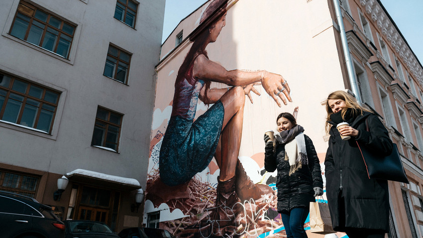 Two women passing Fintan Magee's 'Message'