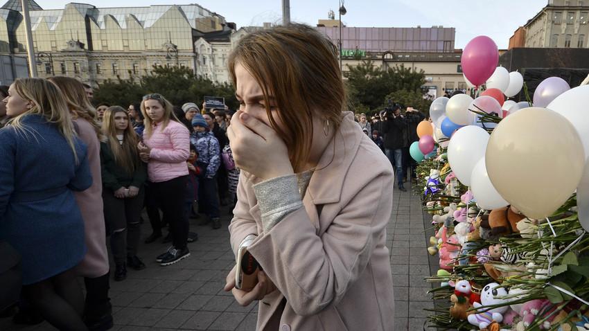 Mulher aos prantos durante evento para homenagear as vítimas da tragédia de Kemerovo. Foram registradas mais 30 reuniões do tipo em toda a Rússia