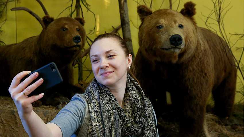 A woman takes a selfie by stuffed brown bears at the Ryazan Kremlin Historical and Architectural Museum-Reserve as she takes part in Museum Selfie Day