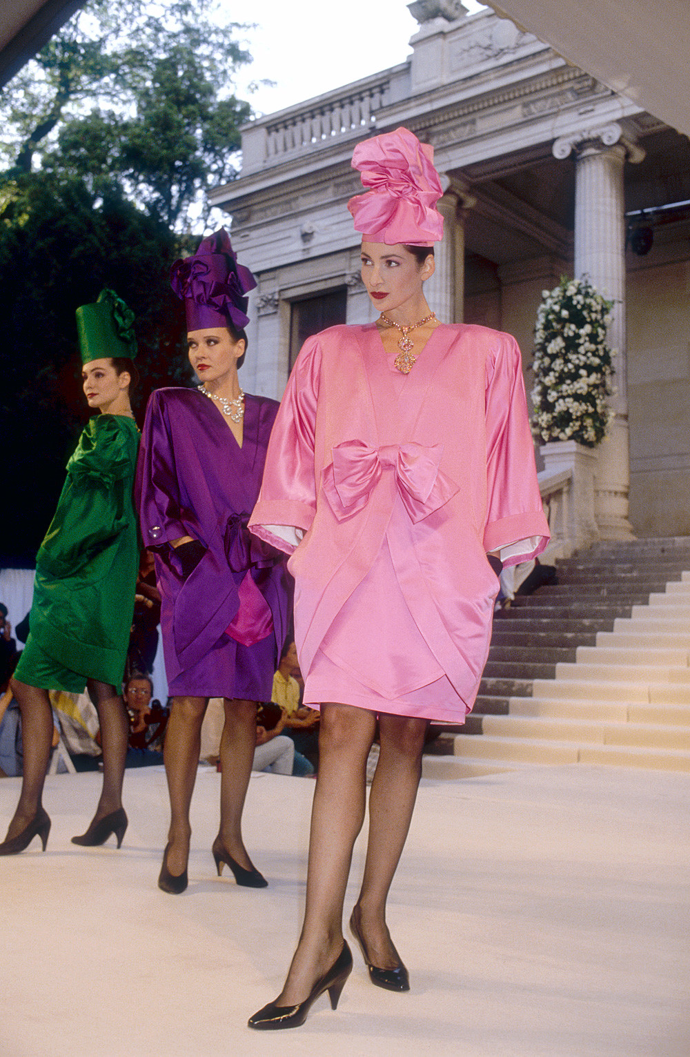 Three fashion models wearing haute couture cocktail dresses and hats by Slava Zaitsev (Autumn-Winter 1988-1989 fashion show in Paris)